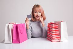 Young Asian woman with shopping bag and blank card. Royalty Free Stock Images