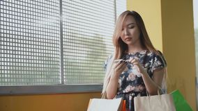 Young asian woman with shopping bags using the smartphone. stock video footage