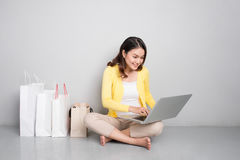 Young asian woman shopping online at home sitting besides row of Royalty Free Stock Photography