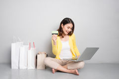 Young asian woman shopping online at home sitting besides row of stock photo