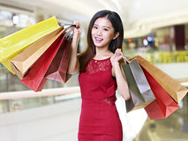 Young asian woman on a shopping spree. Young asian woman on shopping spree carrying paper bags walking in mall, happy and smiling stock photography