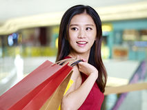Young asian woman on a shopping spree. Young asian woman on shopping spree carrying paper bags walking in mall, happy and smiling stock image