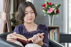 Young asian woman short hair read a book in living room. Close up beautiful young asian woman short hair read a book in living room at home stock photography