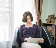 Young asian woman short hair use mobile phone in living room Royalty Free Stock Images