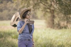 Woman wear hat and carry her guitar in grass field Stock Image