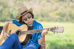 Woman wear hat and playing guitar on pickup truck Stock Photo