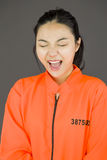 Young Asian woman shouting in excitement and wearing prisoners uniform. Young attractive Asian woman in her 20's shot in studio isolated on a white background Stock Photos