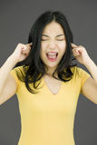 Young Asian woman shouting in frustration. Young attractive Asian woman in her 20's shot in studio  on a white background Royalty Free Stock Images