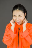 Young Asian woman shouting in frustration in prisoners uniform. Young attractive Asian woman in her 20's shot in studio isolated on a white background Stock Image