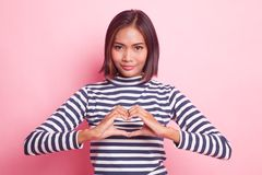 Young Asian woman show heart hand sign. Young Asian woman show heart hand sign on pink background stock photos