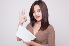 Young Asian woman show OK with a book. Stock Photos