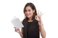 Young Asian woman show OK with a book. Stock Photos