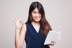 Young Asian woman show OK with a book. Royalty Free Stock Images