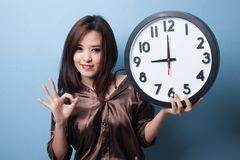 Young Asian woman show OK with a clock. Stock Photos