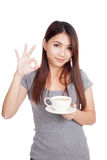 Young Asian woman show OK with cup of coffee Royalty Free Stock Photography
