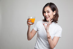 Young Asian woman show OK drink orange juice. Stock Photos