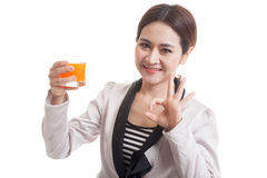 Young Asian woman show OK drink orange juice. Royalty Free Stock Images