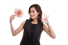 Young Asian woman show OK with a gift box. Royalty Free Stock Photos