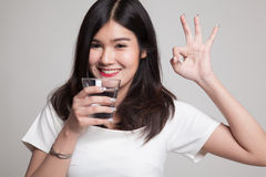 Young Asian woman show OK with a glass of drinking water. Stock Photos