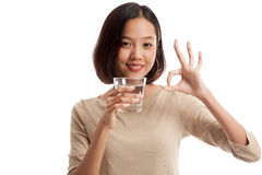 Young Asian woman show OK with a glass of drinking water Stock Photo