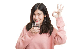 Young Asian woman show OK with a glass of drinking water. Royalty Free Stock Photo