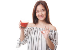 Young Asian woman show OK with tomato juice. Royalty Free Stock Image