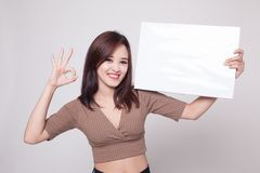 Young Asian woman show OK with  white blank sign. Royalty Free Stock Image