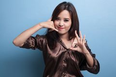 Young Asian woman show with phone gesture and OK sign. Stock Image