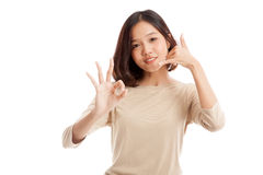 Young Asian woman show with phone gesture and OK sign Royalty Free Stock Photography
