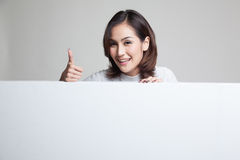 Young Asian woman show thumbs up with blank sign. Stock Photography