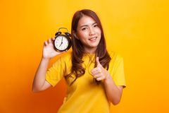 Young Asian woman show thumbs up with a clock in yellow dress Royalty Free Stock Photography