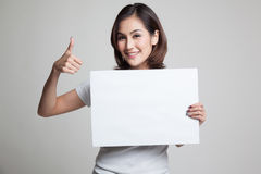 Young Asian woman show thumbs up with  white blank sign. Stock Image