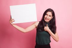 Young Asian woman show thumbs up with  white blank sign. Royalty Free Stock Photography
