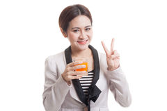 Young Asian woman show victory sign drink orange juice. Stock Photos