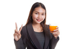 Young Asian woman show victory sign drink orange juice. Stock Image
