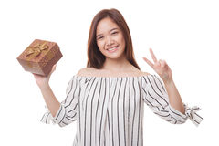 Young Asian woman show Victory sign with a gift box. Royalty Free Stock Image