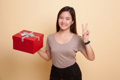 Young Asian woman show Victory sign with a gift box. Young Asian woman show Victory sign with a gift box on beige background Royalty Free Stock Photography