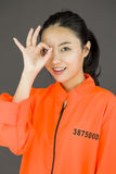 Young Asian woman showing OK sign in prisoners uniform Royalty Free Stock Images
