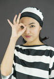 Young Asian woman showing OK sign in prisoners uniform Royalty Free Stock Image