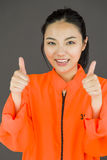 Young Asian woman showing thumb up sign with both hands in prisoners uniform Royalty Free Stock Images