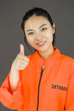 Young Asian woman showing thumb up sign in prisoners uniform Stock Photos