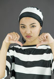 Young Asian woman showing thumbs down sign from both hands in prisoners uniform Royalty Free Stock Photography