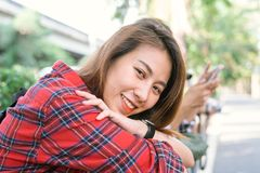 Young Asian women sit and smile along the street enjoying her city lifestyle in a morning of a weekend waiting for outdoor. Royalty Free Stock Photos
