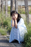 Young asian woman sitting at a barbwire fence. Sad young woman posing alone sitting near barbed wire fence Royalty Free Stock Image