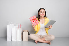 Young asian woman sitting besides row of shopping bags holding r Stock Image