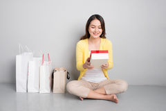 Young asian woman sitting besides row of shopping bags holding r Royalty Free Stock Image