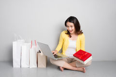 Young asian woman sitting besides row of shopping bags holding r Stock Images
