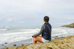 Young Asian woman sitting on a cliff and looking far away at the sea stock images