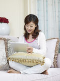 Young asian woman. Asian woman sitting on couch and looking at tablet computer Stock Image