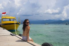 Young Asian woman sitting happy on sea dock at Thailand beach looking at the horizon beautiful marine landscape with mountains enj. Oying holiday relaxed in Royalty Free Stock Images